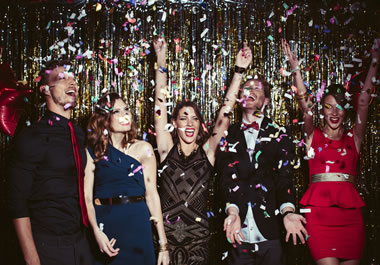 Friends throwing confetti at a New Year's Eve party
