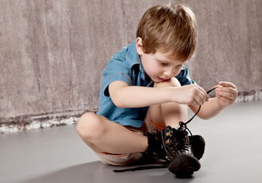 A small boy lacing his shoes