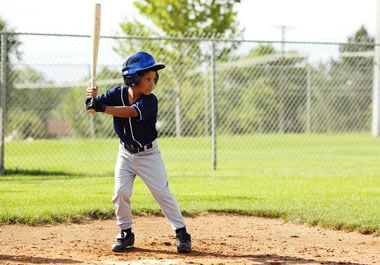 The child is poised and ready to hit the ball.