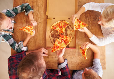 The hungry kids dove right into the pizza.