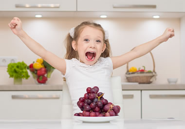 The girl is overly excited about the grapes.