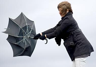 Woman struggling to close an umbrella