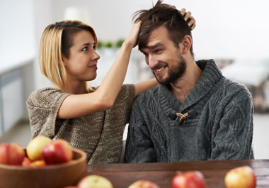 The woman is tousling the man's hair.