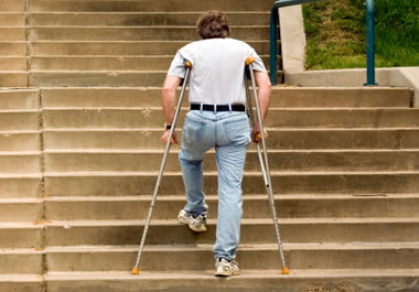Man walking up stairs on crutches