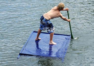A boy standing on a raft