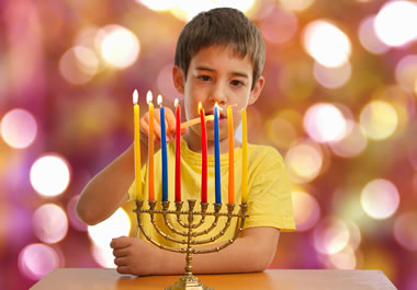 The boy is lighting a Hanukkah menorah.