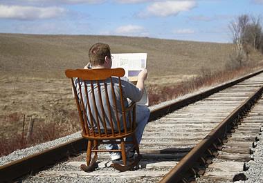 A foolish man reading a newspaper on railroad tracks