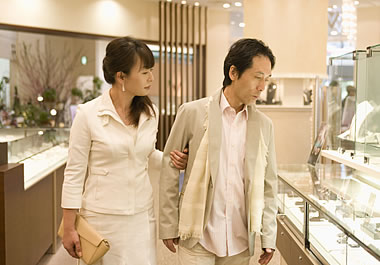 The couple is looking at the jeweler's merchandise.