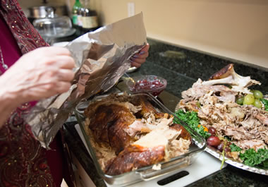 The woman is wrapping up the remainder of the turkey.