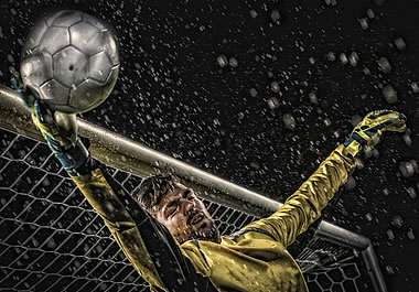 The goalie is deflecting the ball away from the net.