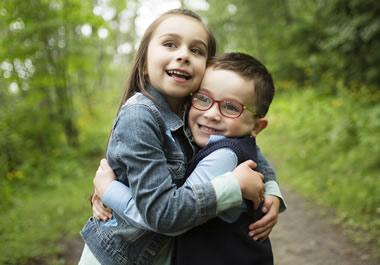 The boy is giving the girl a bear hug.
