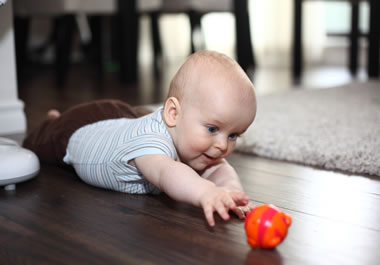 The toy is directly in front of the baby.