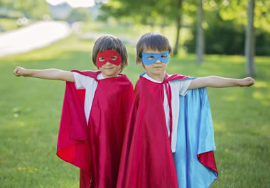 The children are wearing masks and capes.