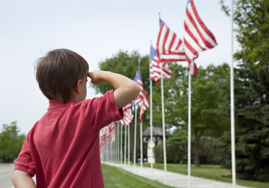 The boy is saluting the American flag.