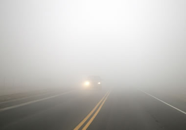 Headlights of a car driving in the fog