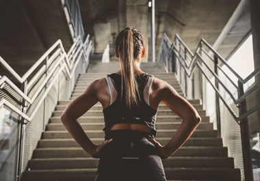 The woman is gathering motivation to climb the stairs.