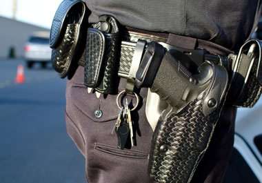 A gun, keys, walkie-talkie, and other devices are clipped onto his belt.