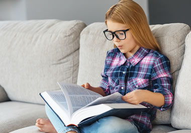 The girl is leafing through the book.