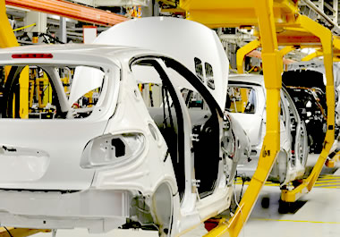 Manufacturing cars on an assembly line.