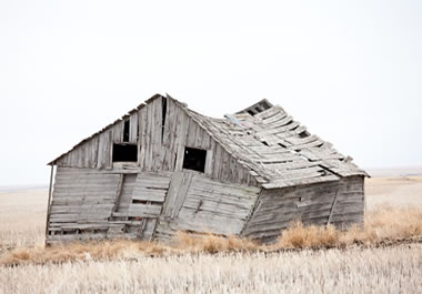 An old, unstable barn that looks ready to fall down