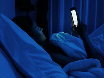 mulher-lendo-telefone-na-cama